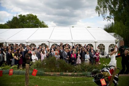 Wedding party gathered in front of a 12mx21m marquee with Georgian window walls