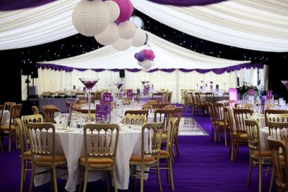 Charity ball with purple carpet and tonal paper lanterns and golden banquet chairs